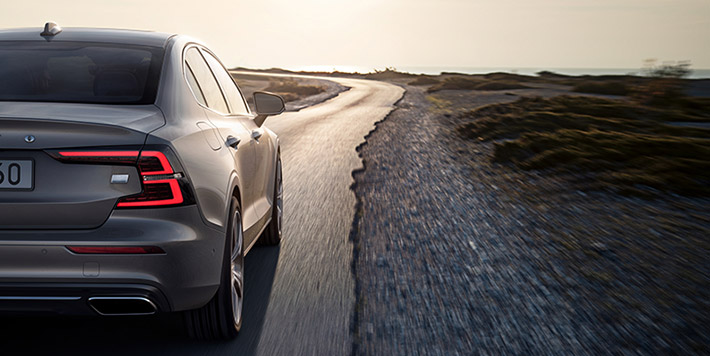 View showing rear of a grey Volvo saloon driving along a semi-metalled road